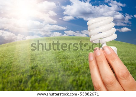 Female Hand Holding Energy Saving Light Bulb Over Arched Horizon of Grass Field, Clouds and Sky. - stock photo
