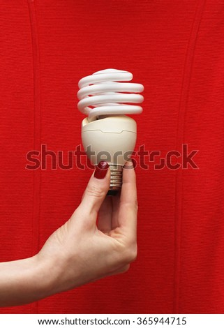 Female hand holding energy saving lightbulb on red background - stock photo