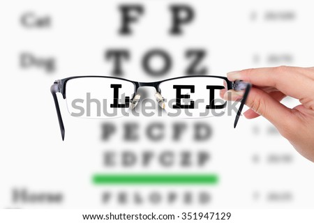 Female hand holding glasses with eyesight test on chart board. - stock photo