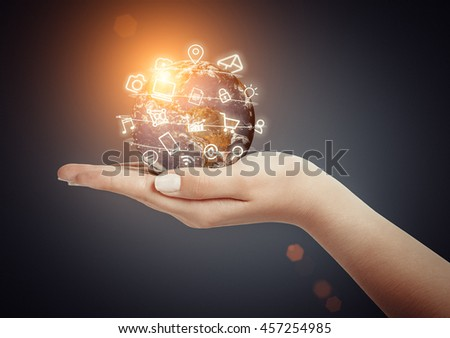 female hand holding globe and media icons fly around