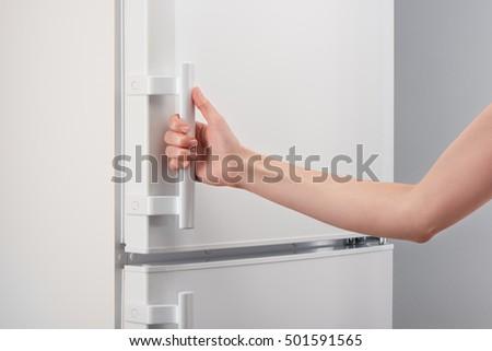 Female hand holding handle of white refrigerator door on gray background & Fridge Handle Stock Images Royalty-Free Images \u0026 Vectors ...