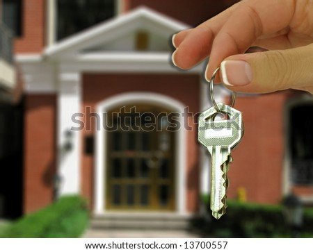 Female hand holding key in front of a house - stock photo