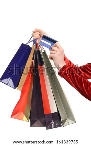 Female hand holding many shopping bags and a credit card. Hand of a woman with shopping bags paying with credit card. Ready for spending. Isolated on white. - stock photo