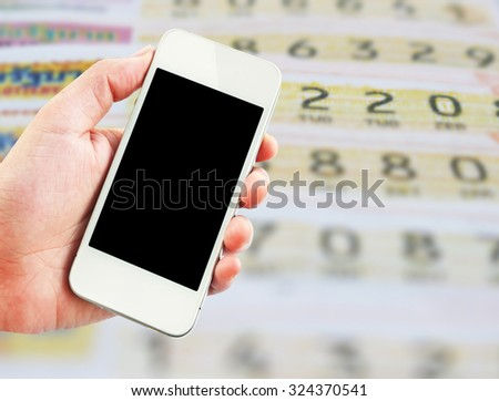 Female hand holding mobile smart phone on Thai lottery tickets blur background, business concept - stock photo
