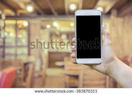 female hand holding mobile smart phone,tablet,cellphone over Blur or Defocus image of Coffee Shop or Cafeteria,Customer at restaurant blur background with bokeh,vintage color,food online call shopping - stock photo