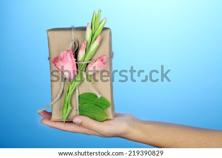Female hand holding natural style handcrafted gift box with fresh flowers and rustic twine, on color background