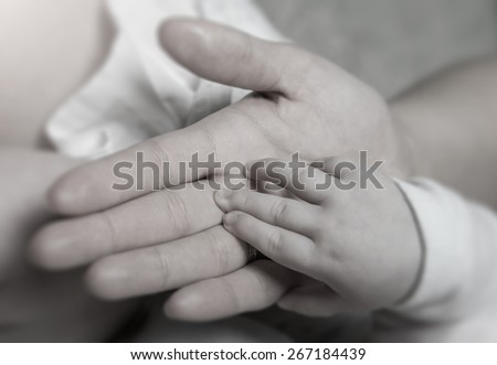 Female hand holding newborn baby's hand, black and white toned