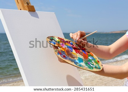 Female hand holding palette and easel with canvas on beach - stock photo