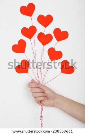 Female hand holding paper balloons, on white wall background - stock photo