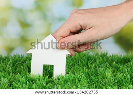 Female hand holding paper house on green background, close up