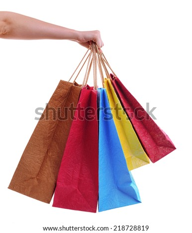 Female hand holding paper shopping bags isolated on white - stock photo
