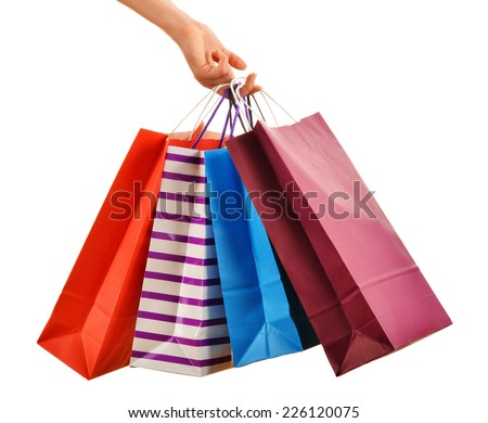 Female hand holding paper shopping bags isolated on white background