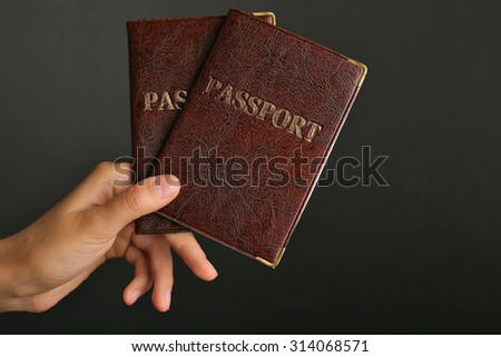 Female hand holding passports on dark background