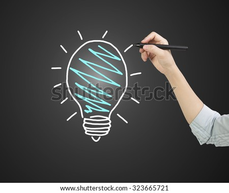 Female hand holding pen drawing light bulb, side view, isolated on black background. - stock photo
