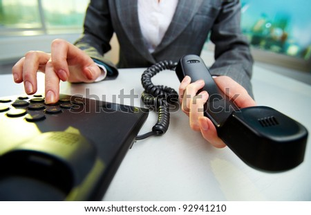 Female hand holding phone receiver and dialing number - stock photo