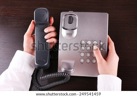 Female hand holding phone receiver and dialing number on wooden background - stock photo