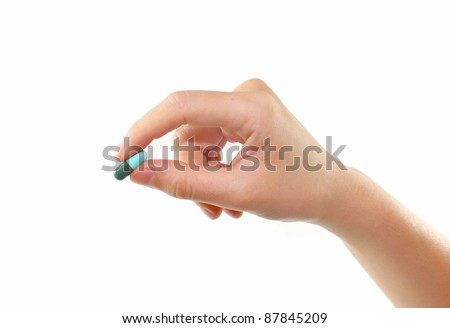 female hand holding pill isolated - stock photo