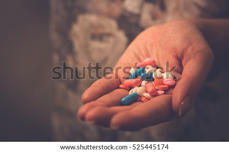 female hand holding pills and tablets. sick woman looking for help