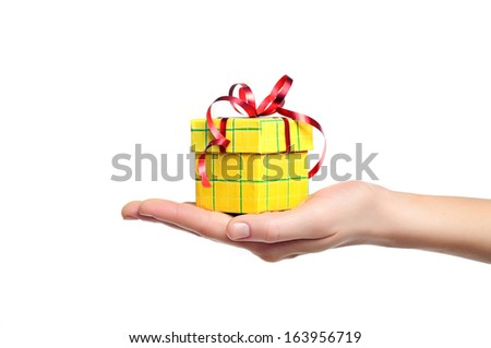 female hand holding red and yellow gift box with a bow isolated on white  - stock photo