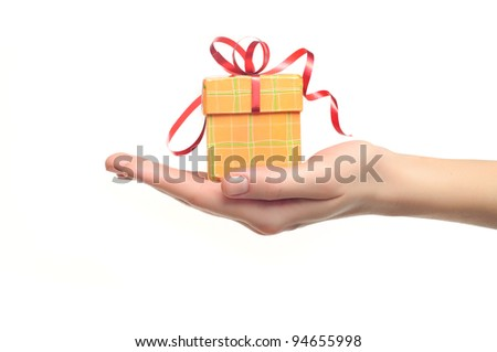 female hand holding red and yellow gift box with a bow isolated on white background - stock photo