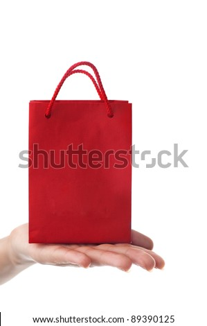 female hand holding red gift bag with present with her fingers - shopping and holiday concept