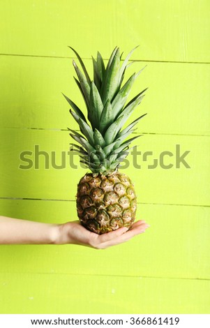 Female hand holding ripe pineapple on a green wooden background - stock photo