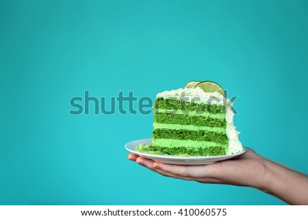 Female hand holding saucer with piece of delicious creamy lime cake on blue background - stock photo