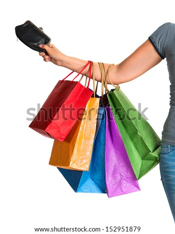 Female hand holding shopping bags and purse on a white background