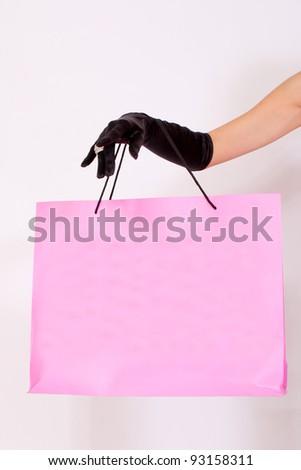 Female hand holding shopping paper bag - stock photo