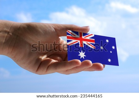 Female hand holding small flag of Australia - stock photo
