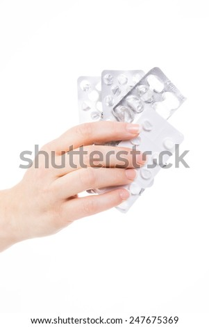 female hand holding some pill blisters against white background - stock photo