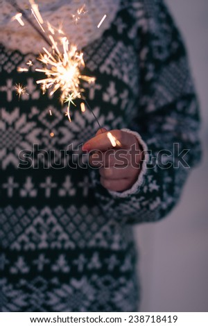 Female hand holding sparkler - stock photo