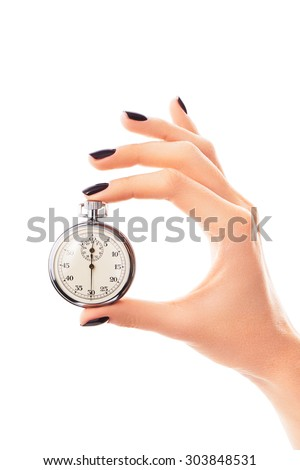 Female hand holding stopwatch set to thirty seconds, with nails covered with black nail polish. Concept of extremely fast drying nail polish - stock photo