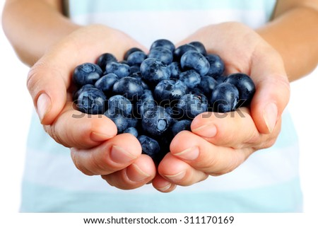 Female hand holding tasty ripe blueberries close up - stock photo