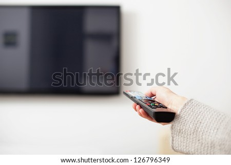 Female hand holding TV Remote Control - stock photo