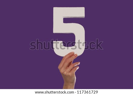 Female hand holding up the number 5 against a purple background conceptual of numbers, measurement, amount, quantity, accounting and mathematics - stock photo