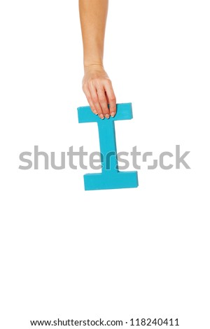Female hand holding up the uppercase capital letter I isolated against a white background conceptual of the alphabet, writing, literature and typeface - stock photo