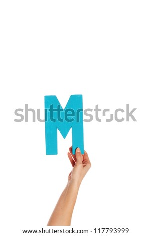 Female hand holding up the uppercase capital letter M isolated against a white background conceptual of the alphabet, writing, literature and typeface - stock photo
