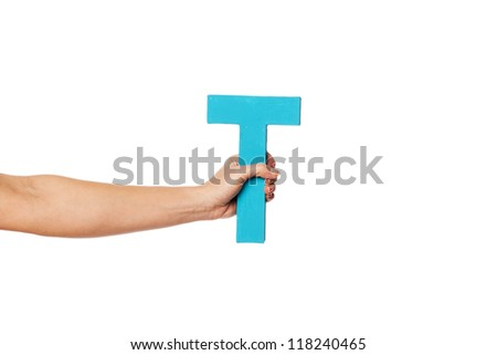 Female hand holding up the uppercase capital letter T isolated against a white background conceptual of the alphabet, writing, literature and typeface - stock photo