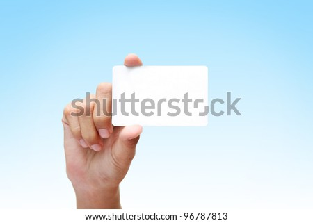 female hand holding white business card on blue background. - stock photo