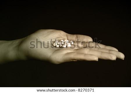 Female hand holding white generic pills - stock photo