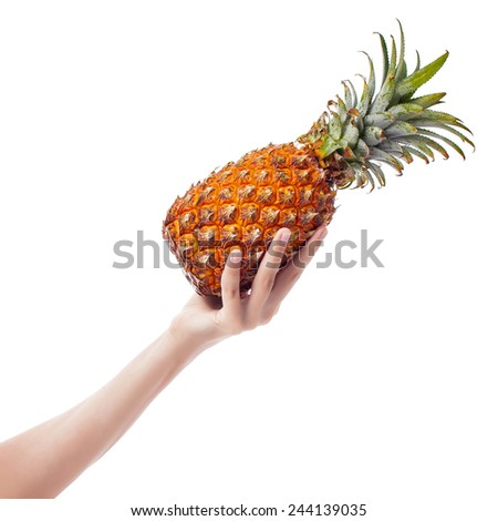 Female hand holds ripe pineapple on white background - stock photo