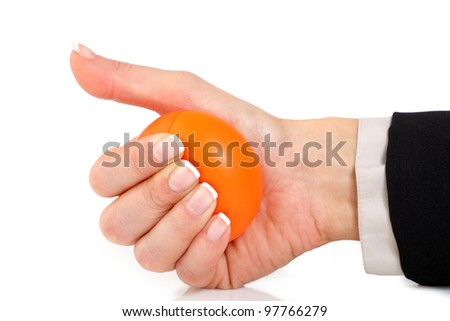 Female hand in a suit squeezing an orange stress ball - stock photo