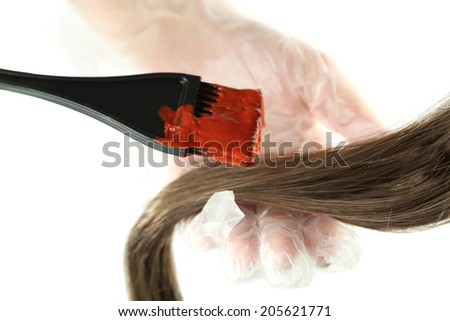 Female hand in gloves dips with  brush for hair coloring, isolated on white - stock photo