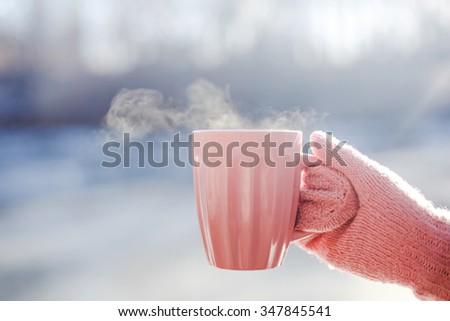 Female hand in mittens holding cup with hot tea or coffee. Tea break. Winter and Christmas time concept