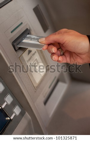 Female hand inserting a bank card at an automatic bank teller machine to withdraw or deposit money - stock photo