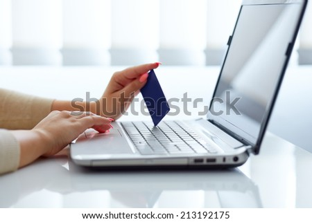 Female hand inserts data into the notebook and holding credit card - stock photo