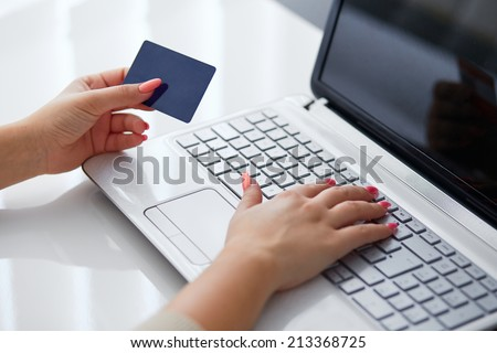 Female hand inserts data into the notebook and holding credit card