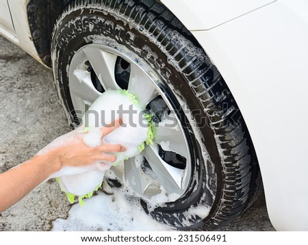 female hand is cleaning car tire with sponge ; selective focus at hand - stock photo