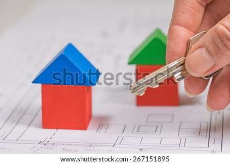 Female hand is holding a house key. On the background  are colorful houses from wooden blocks. Everything is on the blueprint of the house. - stock photo